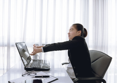 oneself: Successful businesswoman relaxing in her chair at the office with her hands clasped and stretch oneself
