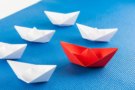 Leadership concept with red paper ship leading among white and blue background Stock Photo
