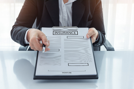 homeowners: young woman in suit in his office showing an insurance policy and pointing with a pen where the policyholder must to sign