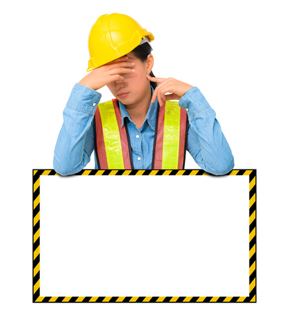 female worker with Protection Equipment, posing behind big white banner, scratching head, looking down and thinking and copy space, isolated on white background