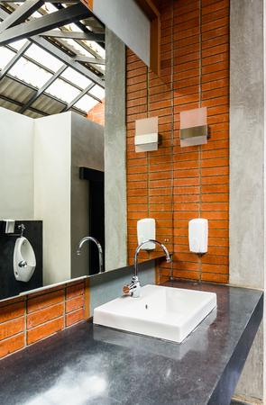 White ceramic bathroom sink in mens bathroom Stock Photo