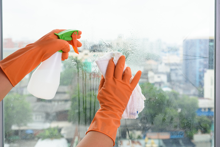 Hand  in gloves cleaning window with rag and cleanser spray at home. housework and housekeeping concept Stock Photo