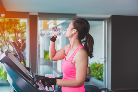 Gym woman working out drinking water by moonwalker fitness machines. Asian female fitness model inside in fitness center. Stock Photo