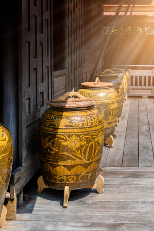 Water jar with wooden Tripod, lid on wooden floor in thai house style