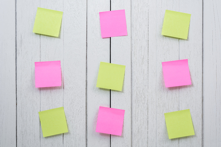 Many colorful sticky note, post note or post-it on white wooden vintage background. space for your text