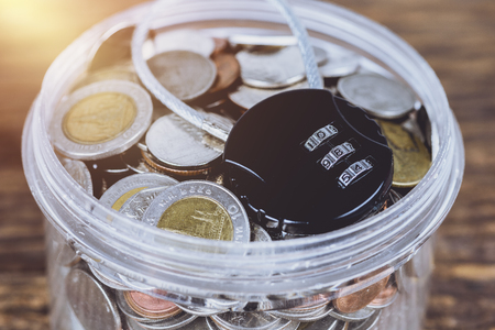 Black security lock with pass-code or password and full coins with jar. Save Money Concept and used for financial protection inferences or other investment messages