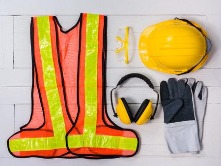 Standard-Konstruktionssicherheitsausrüstung auf weißem Holzhintergrund. Draufsicht, Sicherheit zuerst Konzepte
