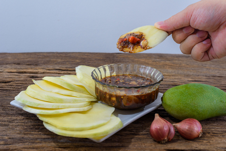 man finger holding sliced green mango with chilli, Red onion in sweet fish sauce nampla wan, thai food on wooden table, Selective Focus