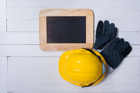 Standard construction safety equipment with Empty chalkboard on white wooden background. top view, safety first concepts Archivio Fotografico