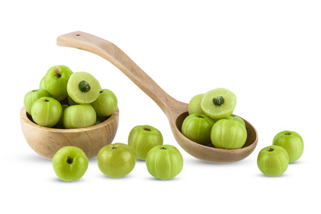 Indian gooseberry in wooden bowl, spoon isolated on white background with clipping path