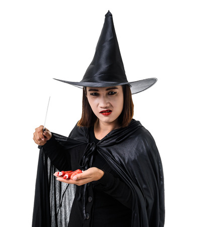 Portrait of woman in black Scary witch halloween costume standing with hat, holding knife and finger in her hand isolated on white background with clipping path Stockfoto