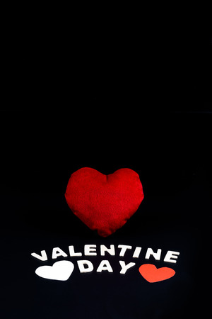 Heart shape and Wooden letters word VALENTINE DAY on black background. Concept of Valentines day Stock Photo