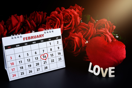 Calendar with red written heart highlight on February 14 with heart shape and Wooden letters word