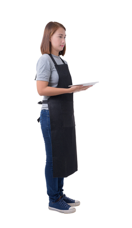 waitress, delivery woman or Servicewoman in Gray shirt and apron. hand holding empty white plate isolated on white background with clipping path Banco de Imagens