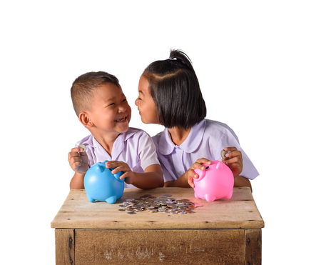 Cute asian country boy and girl in school uniform putting coins into piggy bank isolated on white background with clipping path. Education Savings concepts