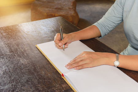 Womans hand signing a guest book with a pen and window light and shadow