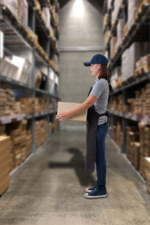 Female staff Lifting parcel boxes with Blurred the background of the warehouse