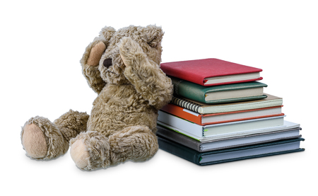 Cute brown bear doll with Many books two hands closed their eyes, showing regret and dismal isolated on white background. Embarrassment with learning concept