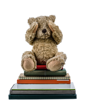Cute brown bear doll Sitting on Many books two hands closed their eyes, showing regret and dismal isolated on white background. Embarrassment with learning concept Banque d'images