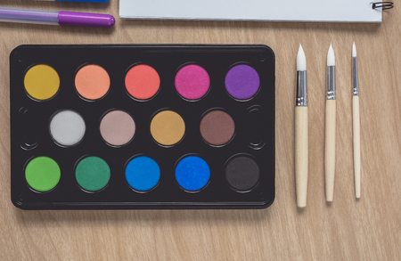 Notepad or notebook with Many colorful pens, paintbrush and Watercolor palette on brown wood table.using for Arts and Education background. Take note on book with paper and concept, copy space for your text