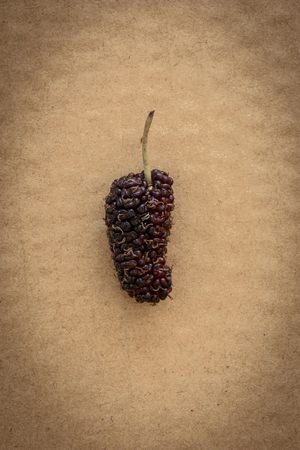 Heap of organic Mulberry fruits on brown cardboard background