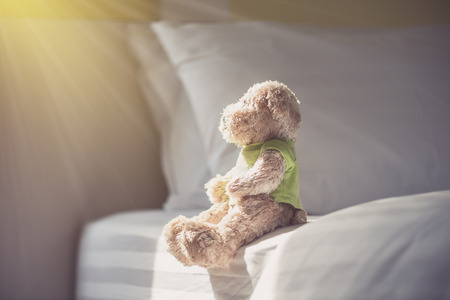 Lonely doll bears on the bed with window light. Sadness concept in vintage color tone