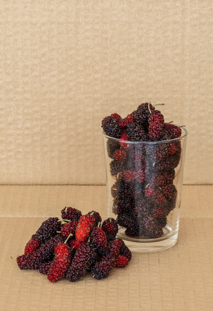 Organic Mulberry fruits in Clear glass on brown cardboard background