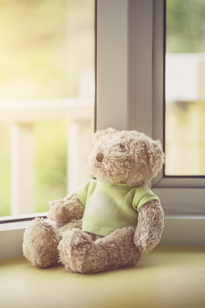 Lonely doll bears near the window with sunlight. Sadness concept in vintage color tone Stock Photo