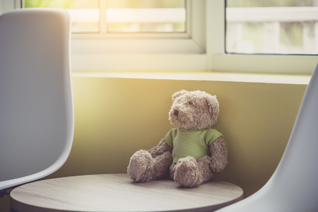 Lonely doll bears near the window with sunlight. Sadness concept in vintage color tone 写真素材