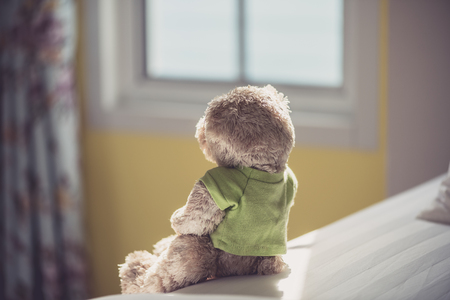 Back view of Lonely doll bears on the bed with window light. Sadness concept in vintage color tone
