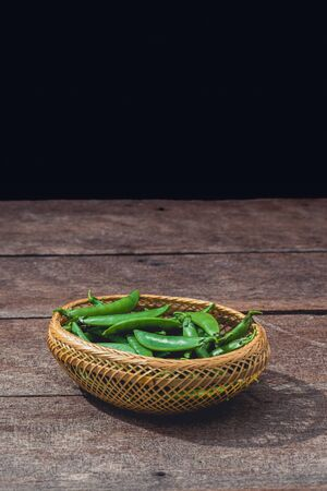Frische grüne Erbsen oder Bohnen im Korb auf Holztisch. Bilder im Retro-Stil anpassen