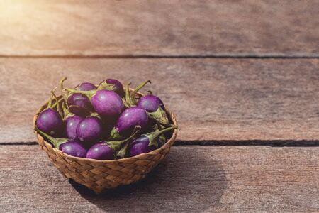 Fresh raw Purple Eggplant in wicker basket on wooden table with coppy space for your text. Customize retro style images 免版税图像