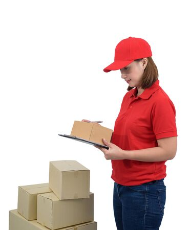 Delivery woman in red uniform with Parcel boxes making notes on delivery receipt clipboard, isolated on white with clipping path. mail, logistics, people and shipping courier service concept 免版税图像