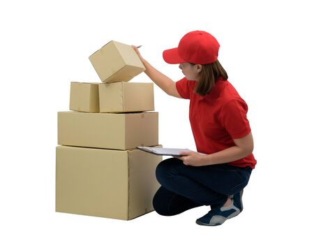 Delivery woman in red uniform with Parcel boxes Check the details consignees with clipboard, isolated on white with clipping path. mail, logistics, people and shipping courier service concept