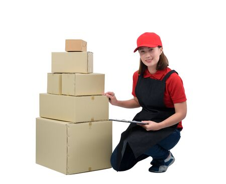 Delivery woman in red uniform with apron and Parcel boxes Check details consignees with clipboard, isolated on white with clipping path. mail, logistics, people and shipping courier service concept