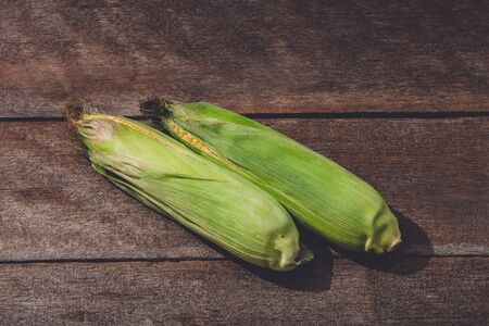 Fresh yellow corn with cobs on rustic wooden table. Customize retro style images
