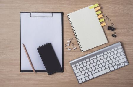 Workspace with diary or notebook and smart phone, clipboard, keyboard, pencil, sticky notes on wooden background. Flat lay, top view office table desk and copyspace