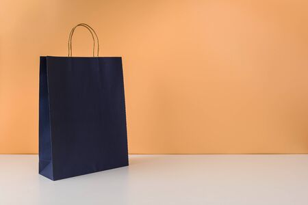 mockup of blank craft package or colorful paper shopping bag with handles on white table and pastel orange background. with copy space for your message Stok Fotoğraf