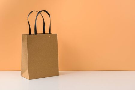 mockup of blank craft package or Brown paper shopping bag with handles on white table and pastel orange background. with copy space for your message Stok Fotoğraf