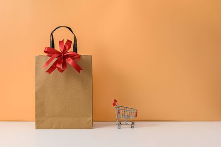 Paper shopping bags and shopping cart or trolley with Red ribbon bow on white table and pastel orange background. with copy space for your message. The concept of selling or shopping online