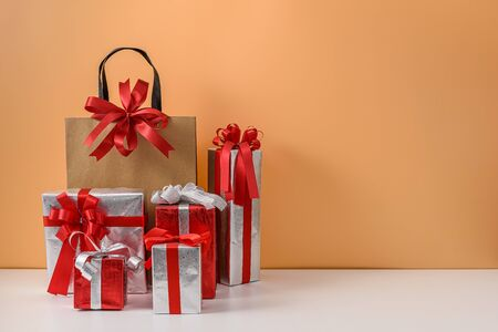 Brown paper shopping bag with Red ribbon bow and many Gift Box on white table and pastel orange background. with copy space for your message. concepts New Years gift or Christmas Stok Fotoğraf