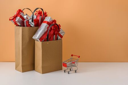 Paper shopping bags and shopping cart, trolley. many Gift Box with Red bow on white table and pastel orange background. with copy space for your message. Shopping New Year's gift, Christmas Concept Stok Fotoğraf - 132118293