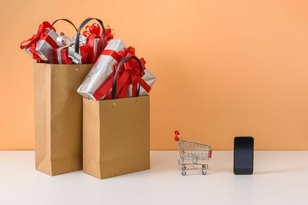 Many Gift Box with Red bow in Shopping bags, shopping cart, smartphone on white table and orange background. with copy space for your message. Shopping online, New Year's gift or Christmas Concept Stok Fotoğraf - 132118688