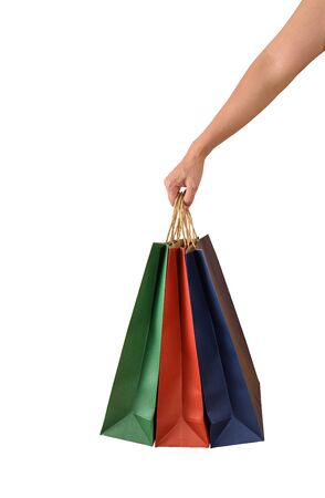 Female hand holding blank colorful papaer shopping bags isolated on white background
