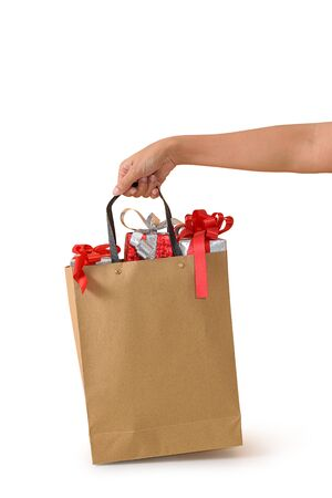 Female hand holding blank brown papaer shopping bags full of gift boxes ornamented isolated on white background