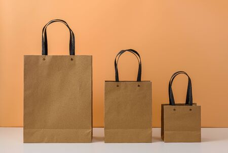 mockup of blank craft package or colorful Brown paper shopping bag with handles on white table and pastel orange background. with copy space for your message