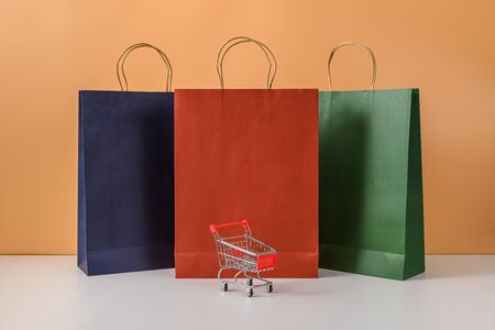 Paper shopping bags and shopping cart or trolley with smartphone on white table and pastel orange background. with copy space for your message. The concept of selling or shopping online