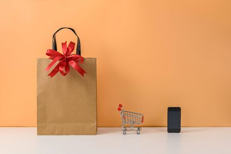 Paper shopping bags and shopping cart or trolley with Red bow and smartphone on white table and pastel orange background. with copy space for your message. The concept of selling or shopping online Stok Fotoğraf