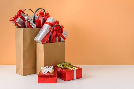 Many Gift Box with Red ribbon bow in Brown paper shopping bag on white table and pastel orange background. with copy space for your message. concepts New Years gift or Christmas