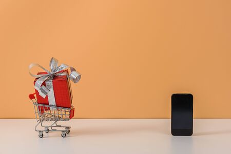 Many Gift Box with Red bow on shopping cart, trolley, smartphone on white table, Orange background. with copy space for your message. Shopping online, New Years gift or Christmas Concept Stok Fotoğraf